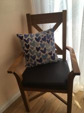 Customer photo 1 - Grasmere oak carver dining chair with brown leather seat pad with a blue seat cushion on it.