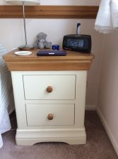 Customer photo 1 - Farmhouse Country Oak Cream Painted Bedside Table in a customers bedroom with a bedside lamp and alarm clock.