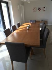 Customer photo 2 - Country Oak 280cm cross leg extending oak dining table with fabric dining chairs in a customers dining room with a bench in the background.