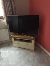 Customer photo 2 - Farmhouse Cream Painted Corner TV Unit with a large widescreen TV.