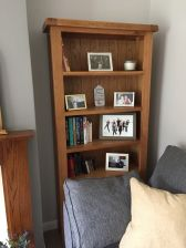 Customer photo 1 - Country oak tall bookcase with drawers in a customers living room with books on display.