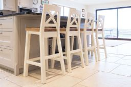 Billy cream painted bar stools next to a customers kitchen island
