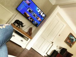 Customer photo 1 - Farmhouse Cream Painted Corner TV Unit in a living room below a huge plasma TV.