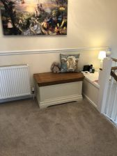 Customer photo 1 - Farmhouse country oak cream painted storage blanket box at the top of a customers stairs on the landing with a cushion and children's toy on it.