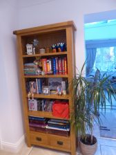 Customer photo 2 - Country oak tall bookcase with drawers in a customers dining room storing lots of customers books.
